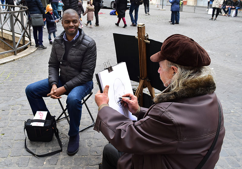 4: In Rome, I sat for about 7 minutes while a street artist created a  caricature of me. It was a hilarious and lovely experience. The artist is  Michael.