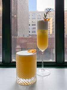Two drinks, each a light amber color with foamy top sit in front of a window overlooking the city
