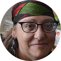 Head shot of a white woman with patterned scarf, glasses, and earrings, and shoulder length hair faces camera.