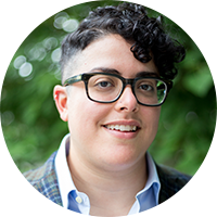 Aimi Hamraie, an olive-skinned non-binary person with short, dark curly hair and rectangular glasses smiles slightly at the camera. They wear a blue shirt, blue and green plaid blazer, and stand in front of a blurred green background