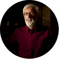 Steven Lubar is a white man with a white hair and beard, wearing glasses and a red shirt, standing in a dark room.