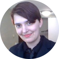Sarah Pawlicki, a white brunette with brown eyes wearing a dark blue blazer, black shirt, and a dark blue tie, smiles in front of a beige wall.