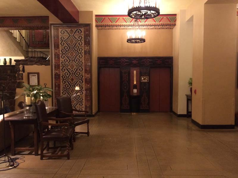 a small lobby with geometric tapestries decorating the walls.