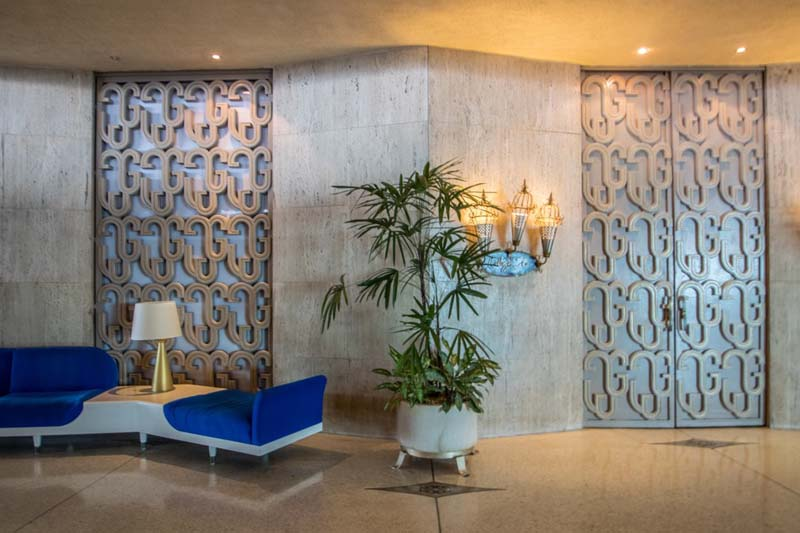 a lobby with a blue and white modernist bench and patterned doors and wall panels